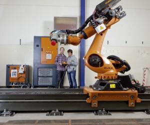 Student David Guthörl (l) und Assistent Alexander Imoberdorf (r) von der Abteilung Maschinentechnik machen sich mit der Bedienung des neuen Knickarm-Roboters vertraut. (Foto: Patrick Kälin)